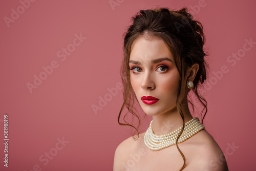 Beauty, fashion portrait of young beautiful woman with pink, fuchsia, color eyes, lips makeup, wearing elegant white pearl necklace, earrings, posing on pink background Fototapeta