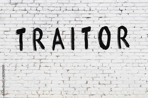 Obraz na płótnie Inscription traitor painted on white brick wall