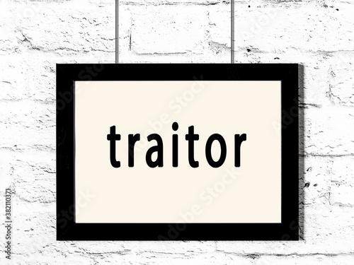 Obraz na płótnie Black frame hanging on white brick wall with inscription traitor