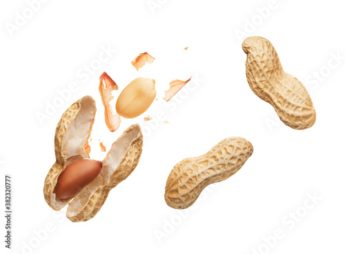 Canvas Print Opened shell peanut and unpeeled peanuts over white background