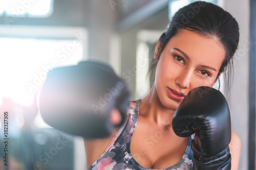Canvas Print Asian woman is throwing Boxing punch into the camera in an indoor gym working out for fitness and healthy lifestle