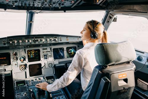 Woman pilot sitting in airplane cockpit, wearing headset. Fototapeta