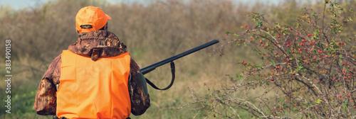 Fotografia Duck hunter with shotgun walking through a meadow.