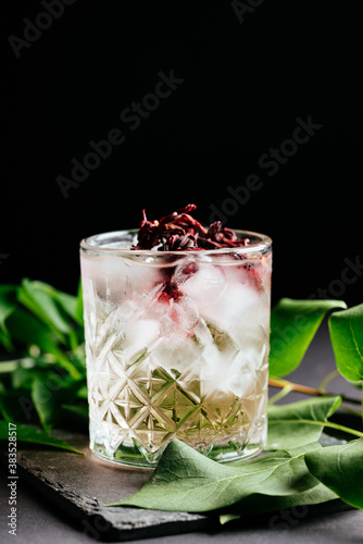 Canvas Print glass of alcoholic coctail with ice on black background