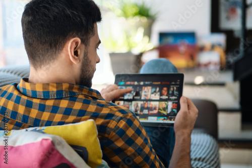 Fotografie, Obraz Man Choosing Movie For Streaming On Tablet Computer