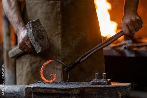 Obraz na plátně Old blacksmith is processing a hot metal object of a spiral shape on the anvil i