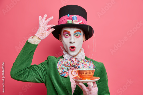 Fotografia Surprised male hatter wears gentlemans clothes holds cup of hot tea pretends to come from wonderland wears vivid makeup celebrates halloween on costume party poses indoor alone