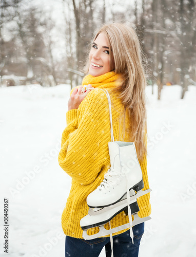 Fotografie, Obraz Winter lifestyle portrait of beautiful blonde girl walking in the snowy park with skates behind the back
