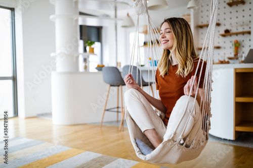 Young woman chilling at home in comfortable hanging chair in front of big window Fototapeta