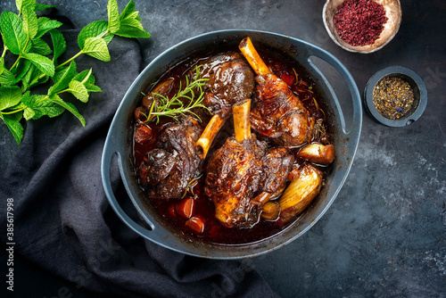 Obraz na plátně Modern style traditional braised slow cooked lamb shank in red wine sauce with s