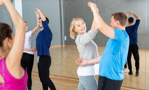 Foto Attractive mature blonde dancing slow ballroom dance in pair during group traini