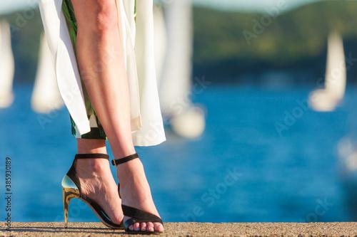 Fototapeta Woman feet in high heels shoes on sea pier