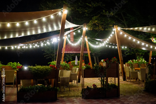 Canvas Print A gazebo decorated with garlands on a warm summer evening