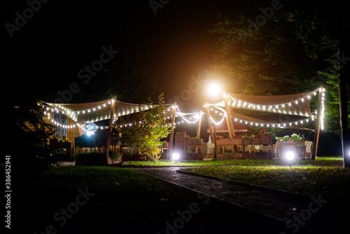 Obraz na plátne A gazebo decorated with garlands on a warm summer evening