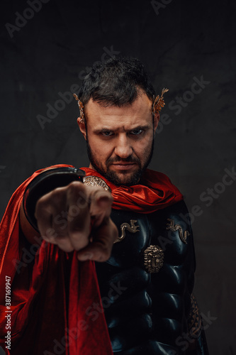 Obraz na płótnie Serious and bearded roman emperor dressed in dark armour and red cloak points finger at camera in dark background