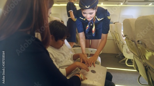 Leinwand Poster Cabin crew provide service to family in airplane