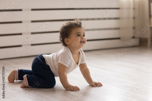 Fototapeta Cute small african American toddler baby child crawl on warm wooden home floor