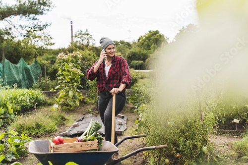 Fototapeta Young woman talking over mobile phone while standing by wheelbarrow in vegetable