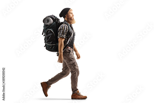 Fototapeta Full length profile shot of a young bearded man with a backpack and hiking equip