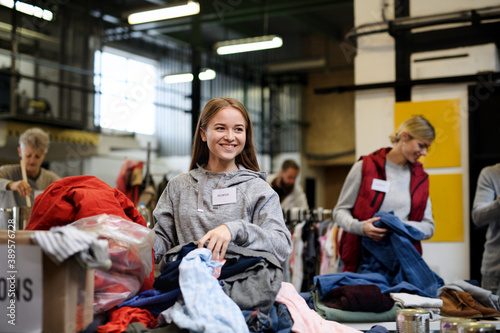 Leinwand Poster Volunteers sorting out donated clothes in community charity donation center, coronavirus concept
