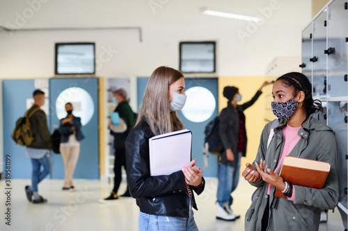 Tableau sur Toile Young students friends with face masks back at college or university, coronavirus concept