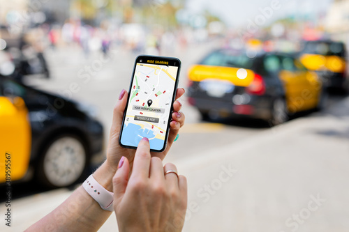 Fototapeta Person using ride sharing app on mobile phone