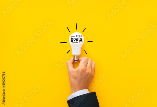 Businessman holding bulb with goals inscription. Business solution, innovation and growth concept.
