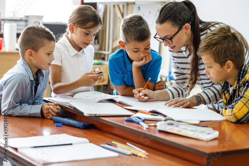 Fototapeta Female teacher helps school kids to finish they lesson