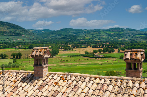 Fotografering Tile rooftop with chimney in Umbria countryside