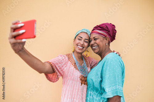 Canvas Print Happy african mother and adult daughter taking a selfie with mobile phone while