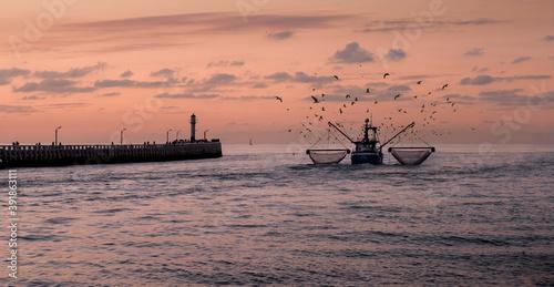Fotografiet Fishing boat sailing next to the old wooden pier of Nieuwpoort in Belgium