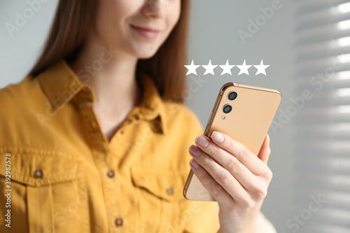 Woman leaving review online via smartphone indoors, closeup Fototapet