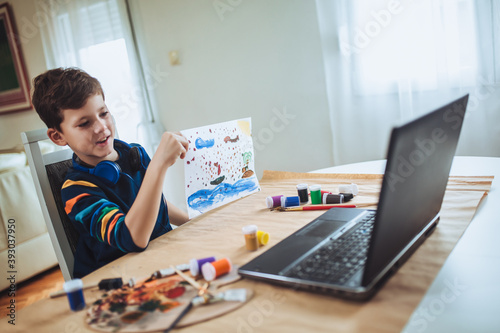 Wallpaper Mural Focused boy painting and watching online course on laptop while practicing at home