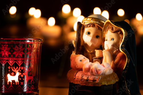 Fototapeta Christmas nativity scene with delicate figures in the new normal of the coronavirus or covid-19