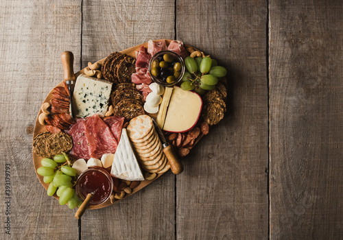 Photo Top view of charcuterie board of meat, cheese, crackers on wood table