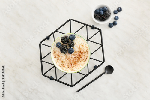 Fototapeta Bowl of tasty rice pudding with berries on white table