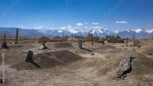 Kyrgyz graveyard with snow-capped moutains in the background near Karakul lake, Murghab district, Gorno-Badakshan province, in the high Pamirs of Tajikistan