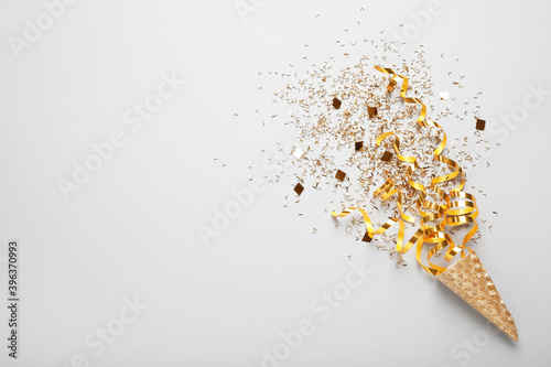 Vászonkép Golden confetti and streamers with party cracker on white background, top view