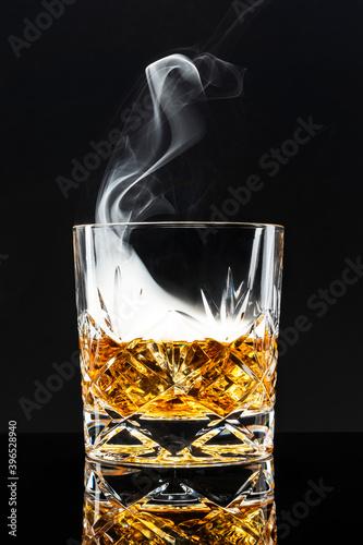 Fototapeta Smoked whisky cocktail on black background