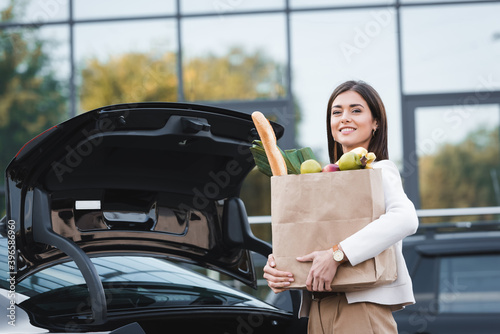 Canvas Print woman looking at camera while standing near open car trunk while holding shoppi