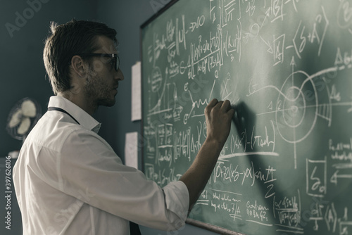 Fotografiet Young smart mathematician drawing on the chalkboard