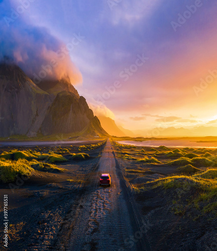 Fotografia Gravel road at sunset with Vestrahorn mountain and a car driving, Iceland