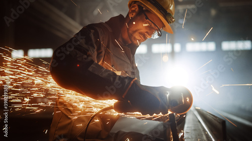 Fotografia, Obraz Heavy Industry Engineering Factory Interior with Industrial Worker Using Angle Grinder and Cutting a Metal Tube