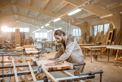 Canvas Print Handsome carpenter in uniform gluing wooden bars with hand pressures at the carp