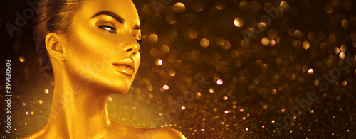 Golden skin make-up, Woman face portrait closeup. Model girl with holiday golden Glamour shiny professional make up. Gold jewellery, jewelry, accessories. Beauty gold metallic body, fashion Xmas art