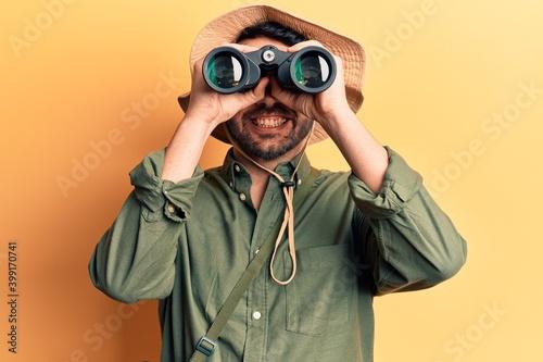 Valokuva Young hispanic man wearing explorer hat holding binoculars looking positive and