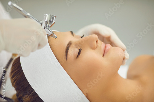 Carta da parati Smiling womans face getting oxygen therapy or jet peeling from cosmetologist