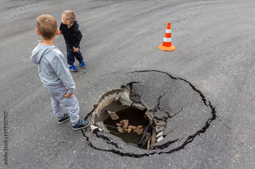Fotografie, Obraz Children play on road near huge deep sinkhole in asphalt surface