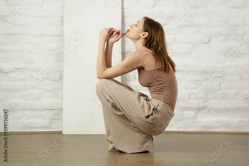 Fashionable woman posing in beige camisole shirt and wide legs beige pants Fototapeta