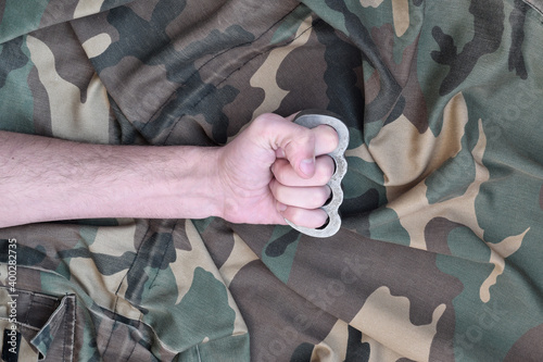 Fototapeta Male fist with brass knuckles on the background of a camouflage jacket